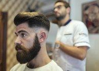 Barbiere e hipster cliente in un barbiere — Foto stock
