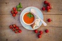 Чаша Томатный крем-суп, украшенный с листьями базилика и переработке деревянной ложкой — стоковое фото
