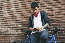 Teenager with a fixie bike texting on smartphone leaning on brick wall — Stock Photo