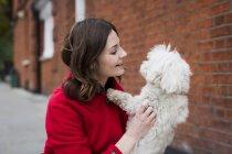 Souriant jeune femme face à son chien — Photo de stock