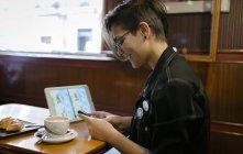 Junge Frau mit digital-Tablette sitzen in einem Café mit Blick auf ihr smartphone — Stockfoto