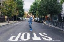 USA, New York City, Williamsburg, mulher de jeans dungarees posando na rua — Fotografia de Stock