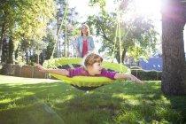 Матір з дочкою на гніздо гойдалки в саду — стокове фото
