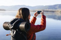 Spain, Catalunya, Girona, female hiker taking a cell phone picture at a lake — Stock Photo