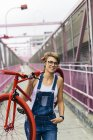 USA, New York City, Williamsburg,  woman carrying red racing cycle on her shoulder on Williamsburg Bridge — Stock Photo