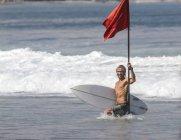 Серфер, удерживая красный флаг в океане — стоковое фото