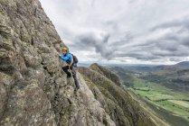 UK, Lake District, Great Langdale, man scrambling at Pike of Stickle — Stock Photo