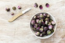 Red brussels sprouts in bowl with knife on wooden surface — Stock Photo