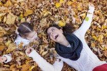 Menina feliz com a mãe deitada nas folhas de outono — Fotografia de Stock