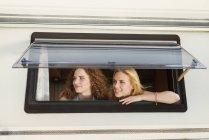 Zwei Freundinnen, die durch das Fenster des Wohnwagens schauen und etwas beobachten — Stockfoto