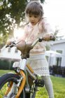 Girl riding bicycle on lawn in garden — Stock Photo