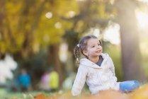 Menina feliz sentado no prado outonal — Fotografia de Stock