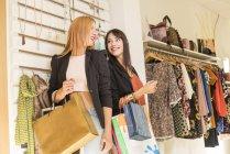 Young women in fashion boutique having fun — Stock Photo