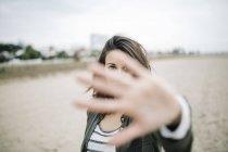 Giovane donna guardando attraverso la sua mano tesa — Foto stock