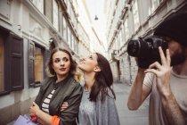 Österreich, Wien, drei Touristen erkunden die Altstadt, junger Mann Fotografieren — Stockfoto