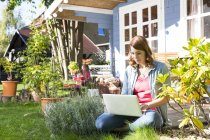 Giovane donna che utilizza computer portatile nel giardino — Foto stock