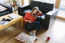 Jeune femme assise sur le sol de son salon regardant tablette numérique — Photo de stock
