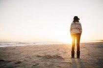 Женщина стоит на пляже зимой — стоковое фото