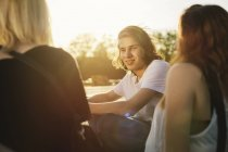 Friends sitting together outdoors at sunset — Stock Photo