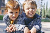 Due ragazzi felici su un'altalena al parco giochi — Foto stock