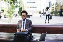 Giovane uomo d'affari sorridente con computer portatile e notebook sulla panchina — Foto stock