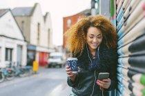 Femme souriante avec café pour aller la musique audience avec smartphone et écouteurs — Photo de stock