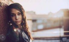 Ritratto di donna in piedi vicino al muro e guardando la macchina fotografica — Foto stock