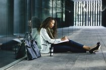 Молодой предприниматель, сидя на открытом воздухе записи в папке — стоковое фото