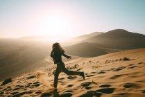 Namibia, Namib Desert, Sossusvlei, Woman running down the Dune at sunrise — Stock Photo
