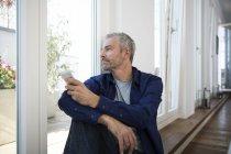 Hombre maduro trabajando desde casa usando un teléfono inteligente - foto de stock