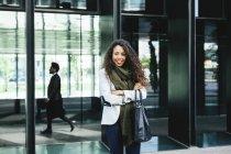 Porträt einer selbstbewussten jungen Geschäftsfrau mit Geschäftsmann im Hintergrund — Stockfoto