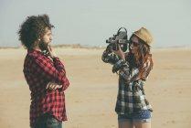 Испания, El Puerto de Santa Maria, молодая женщина снимает своего бойфренда на пляже — стоковое фото