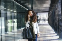 Young woman talking on cell phone outdoors — Stock Photo