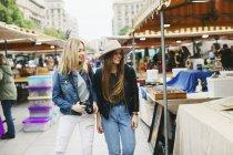 España, Barcelona, dos jóvenes caminando en el mercadillo - foto de stock