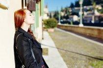 Італія, Верона, молода жінка, притулившись стіни будинку в сонячному світлі — стокове фото