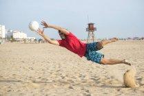 Испания, Кадис, Эль Пуэрто де Санта Мария, человек играть в футбол на пляже — стоковое фото