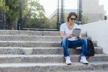 Hombre sentado en los pasos usando tableta digital - foto de stock