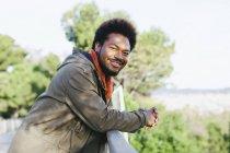 Портрет усміхнений юнак, спершись на перила — стокове фото