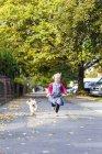 Garota correndo com vira-lata em pavimento — Fotografia de Stock