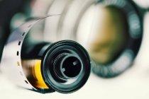 Negative Film und Objektiv im Hintergrund, Nahaufnahme — Stockfoto