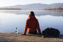 Испания, Каталония, Жирона, туристка отдыхающая на пристани у озера, наслаждаясь природой — стоковое фото