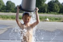 Boy splashing himself with a bucket of water in summer — Stock Photo
