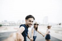 Man holding hands with friends — Stock Photo
