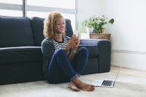 Woman sitting on carpet and using smartphone — Stock Photo
