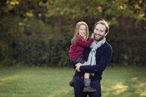 Сміючись чоловік тримає маленькою дочкою на руки — стокове фото