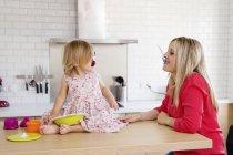 Мати і дочка мало на кухні, граючи з посудом — стокове фото