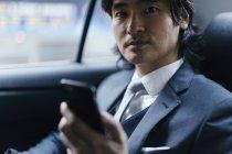 Portrait d'homme d'affaires sur le siège arrière de voiture avec téléphone portable — Photo de stock