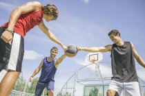 Three young men playing basketball at daytime — Stock Photo