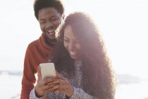 Portrait of happy young couple with smartphone at backlight — Stock Photo