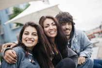Portrait of three happy friends embracing outdoors — Stock Photo